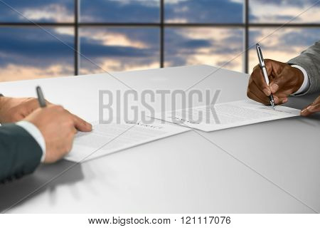 Businessmen sign contracts at sunset.