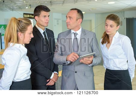 Supervisor with hotel staff, holding tablet