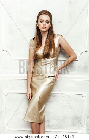 Fashion portrait of young sexy woman with hairstyle wearing golden dress