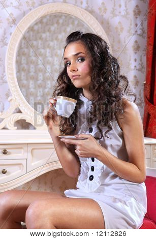 sad young woman sitting on armchair drinking tea poster