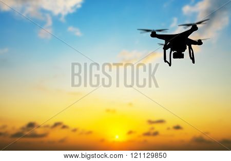 Flying silhouette of drone against sunset