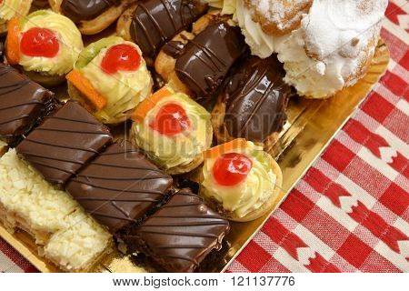 Eclair And A Lot Of Cakes On A Table