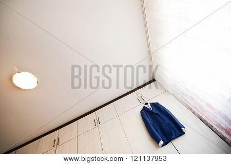 Blue Suit With Shirt Hanging From A Wooden Cupboard