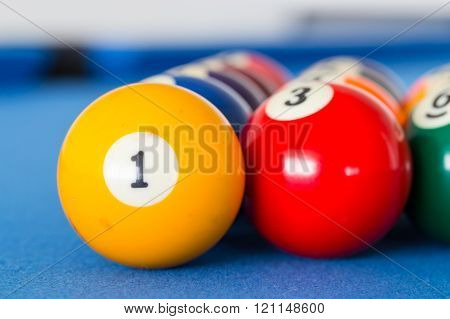 Yellow Billiard Ball Number One And Other Colorful Balls Placed In A Row On A Table