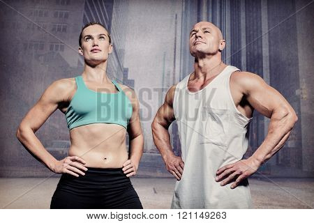 Low angle view of confident athletes with hands on hip against urban projection on wall