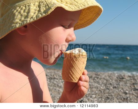 child eating ice-cream on a beach poster