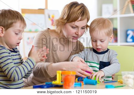 woman teaches kids handcraft at kindergarten or playschool