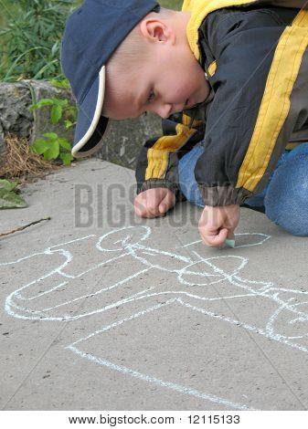 child drawing a chalk on asphalt