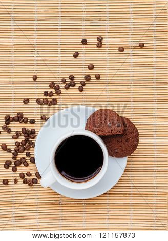 Top view of chocolate cookies and cup of coffee on the table