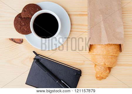 Top view of croissant, coffee and black notebook on wooden table
