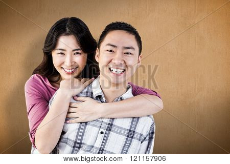 Smiling man gives girl a piggy back against orange background