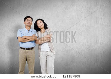 Smiling couple with arms folded against white and grey background