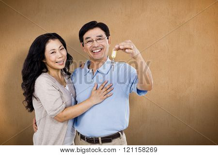 Smiling couple holding a set of keys against orange background