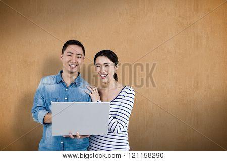 Portrait of couple using laptop against orange background