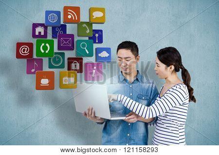 Couple using laptop against blue background
