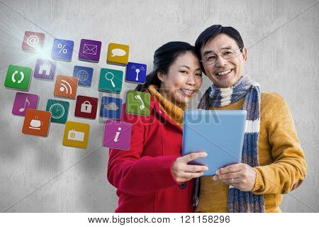 Asian couple on balcony using tablet against white and grey background