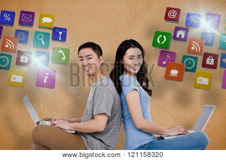 Portrait of young happy couple using laptop while sitting against orange background