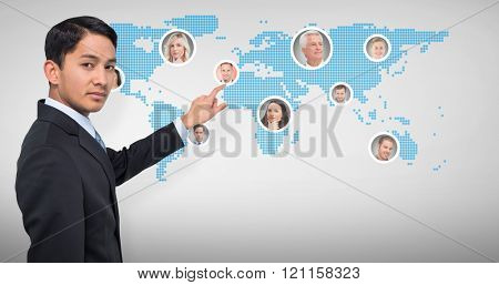 Stern asian businessman pointing against grey vignette