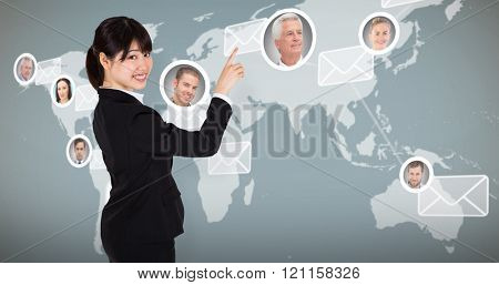 Smiling businesswoman pointing against map with emails
