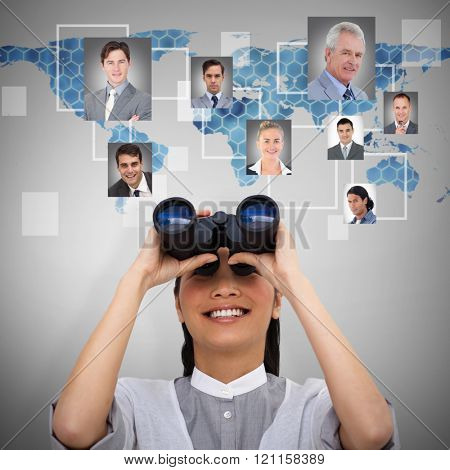 Visionary businesswoman looking through binoculars against background with hexagons and world map