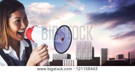 Businesswoman shooting through a megaphone against bridge over city