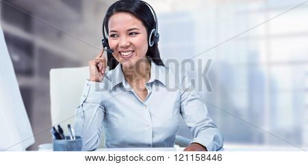 Smiling businesswoman using headset against modern room overlooking city