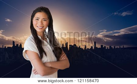 Casual businesswoman looking at camera with arms crossed against picture of city by sunrise