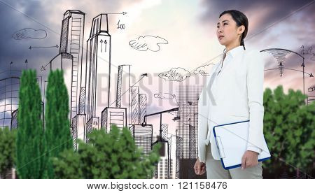 Smiling businesswoman holding clipboard against city plan