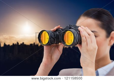 Brunette businesswoman looking through binoculars against picture of city by sunrise