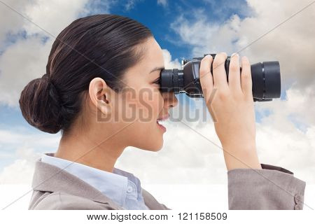 Side view of a businesswoman looking through binoculars against blue sky