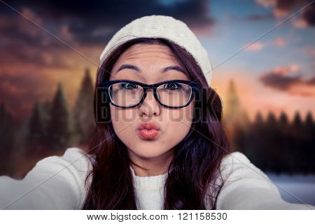 Asian woman making faces against fir tree forest in snowy landscape