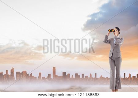Portrait of a brunette businesswoman looking through binoculars against sandy path leading to large urban city