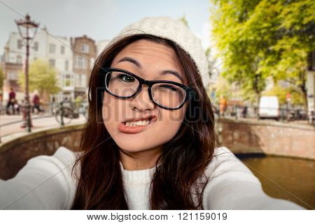 Asian woman making faces against bridge in amsterdam