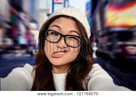 Asian woman making faces against blurry new york street