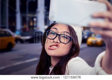 Asian woman making faces and taking selfie against blurry new york street