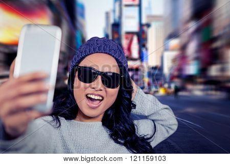 Asian woman taking selfie against blurry new york street