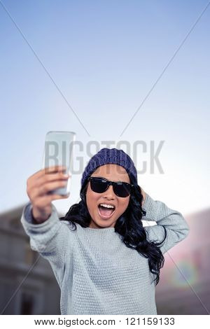 Asian woman taking selfie against low angle view of city buildings on sunny day