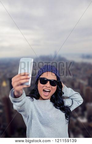 Asian woman taking selfie against new york