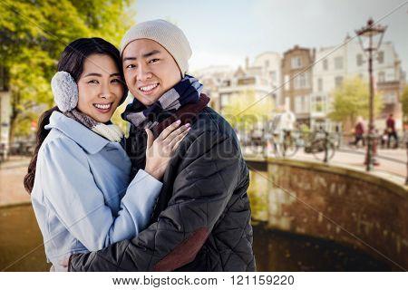 Portrait of couple embracing against bridge in amsterdam