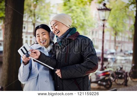 Couple laughing at their pictures taken on smartphone against canal in amsterdam