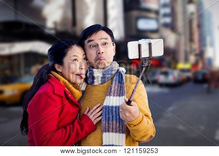 Older asian couple on balcony taking selfie against blurry new york street