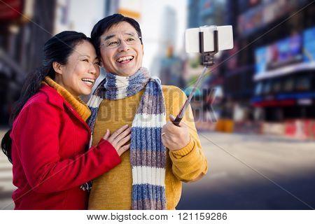 Older asian couple on balcony taking selfie against blurry new york street