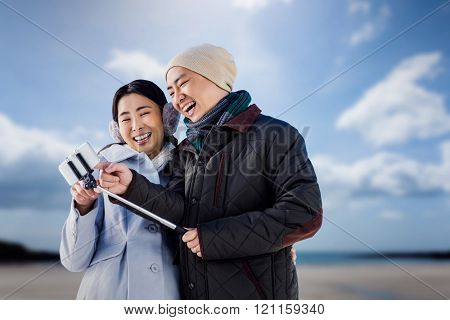 Couple laughing at their pictures taken on smartphone against beach with blue sky