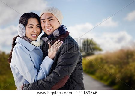 Portrait of couple embracing against country road