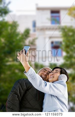 Cute couple taking selfie against low angle view of city building