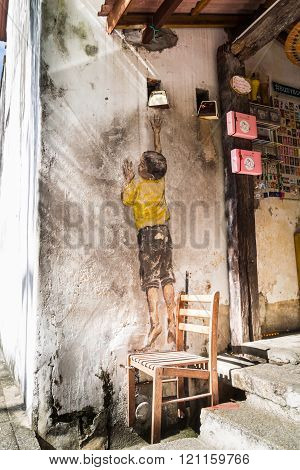 PENANG, DECEMBER 16, 2015:  Mural artwork by artist Ernest Zacharevic entitled Boy On Chair. The mur