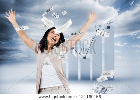 Smiling woman throwing money around against view of percentage on graph
