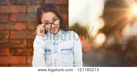 Asian woman holding eyeglasses against wall of a house