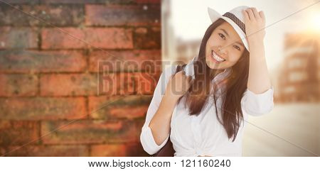 Woman with casual clothes holding her hat against wall of a house