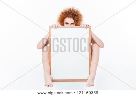 Redhead naked woman with curly hair sitting on the floor with blank board and looking at camera isolated on a white background